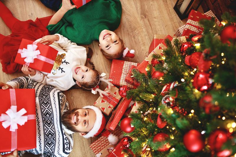 . happy family mother, father and child  with gifts near   Christmas tree at home stock photos