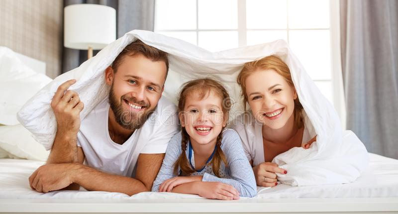 Happy family mother, father and child  laughing, playing and smiling in bed   at home royalty free stock images