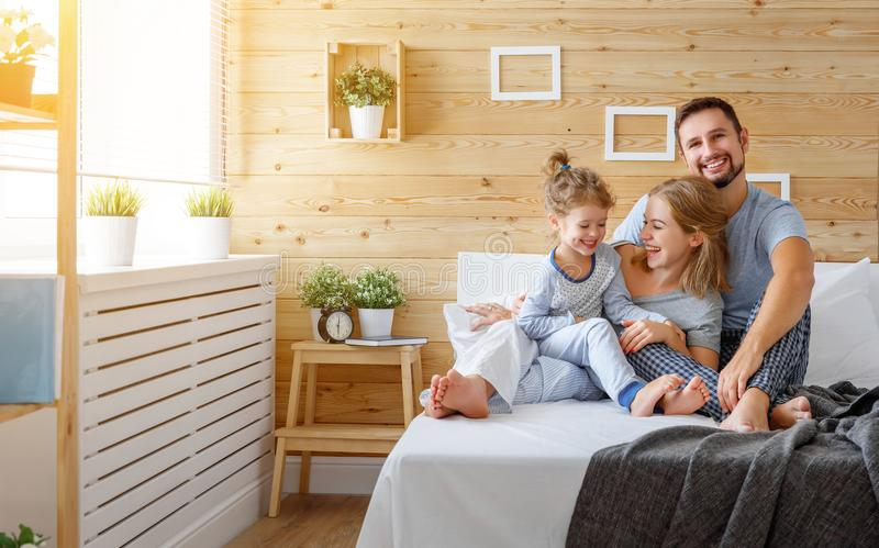 Happy family mother, father and child laughs in bed stock photos