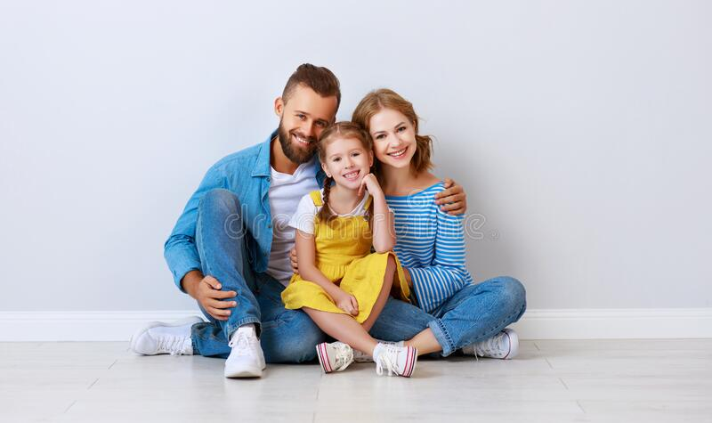 Happy family mother father and child  near an empty brick wall royalty free stock images