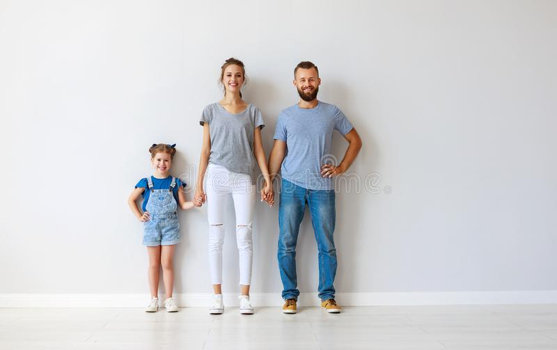 Happy family mother father and child  near an empty wall. Happy family mother father and child daughter near an empty wall stock photos