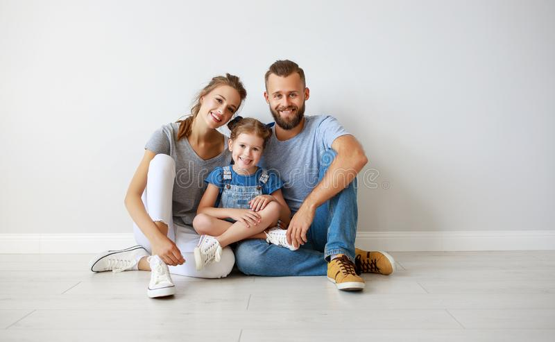 Happy family mother father and child  near an empty wall royalty free stock photo