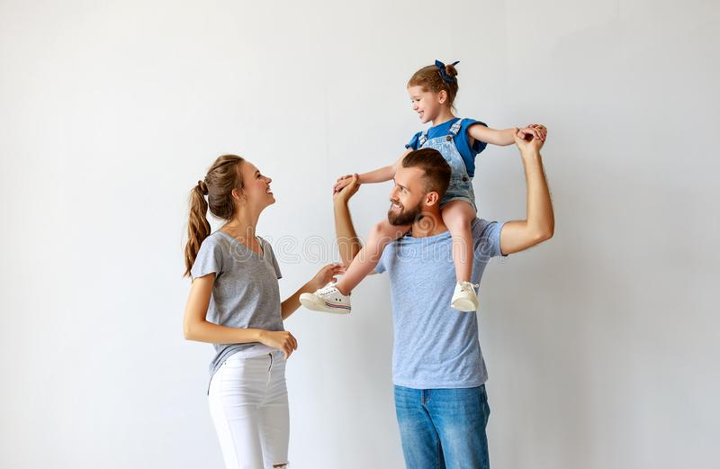 Happy family mother father and child  near an empty wall stock photos