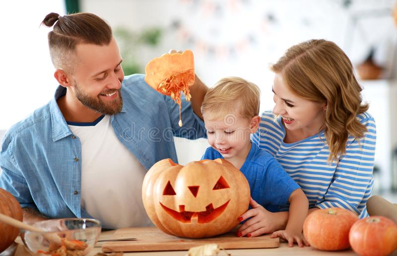Happy  family mother father and child son prepare for Halloween decorate  home with pumpkins and  laughing, play and scare  with royalty free stock photos