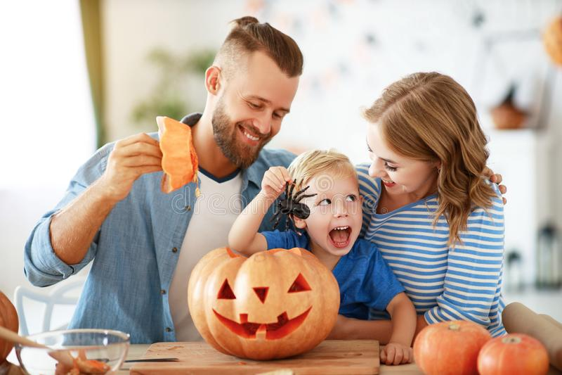 Happy  family mother father and child son prepare for Halloween decorate  home with pumpkins and  laughing, play and scare  with royalty free stock image