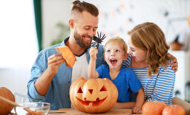 Happy  family mother father and child son prepare for Halloween decorate  home with pumpkins and  laughing, play and scare  with. Happy  family mother father and royalty free stock photo