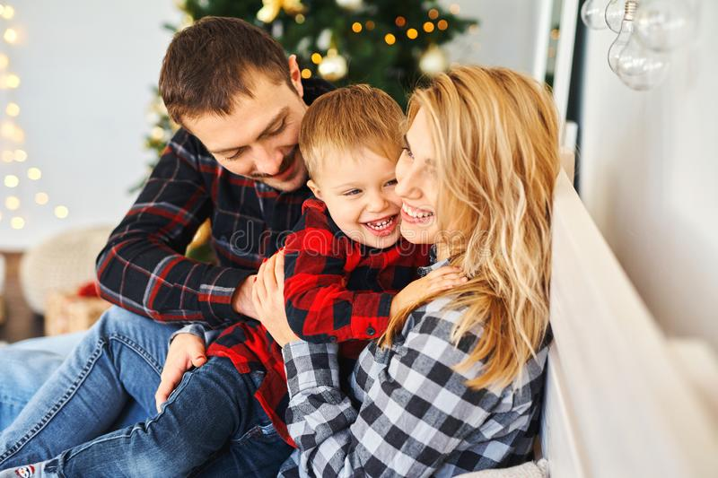 Happy family mother, father, child sonspending time together in bed at home. stock photography