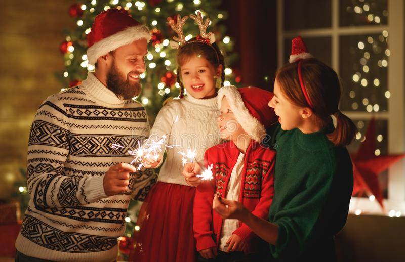 Happy family mother, father and children celebrate Christmas   light sparklers stock photos