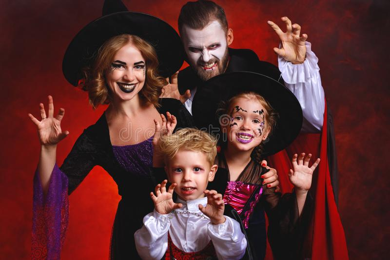 Happy family mother father and children in costumes and makeup on  Halloween on dark red background stock photography