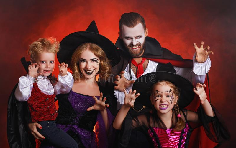 Happy family mother father and children in costumes and makeup on  Halloween on dark red background stock photo