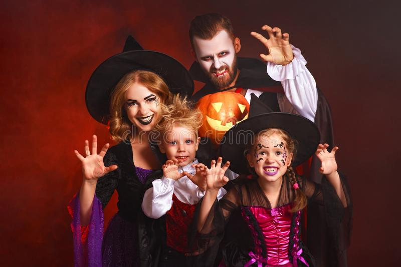 Happy family mother father and children in costumes and makeup on  Halloween on dark red background royalty free stock photo