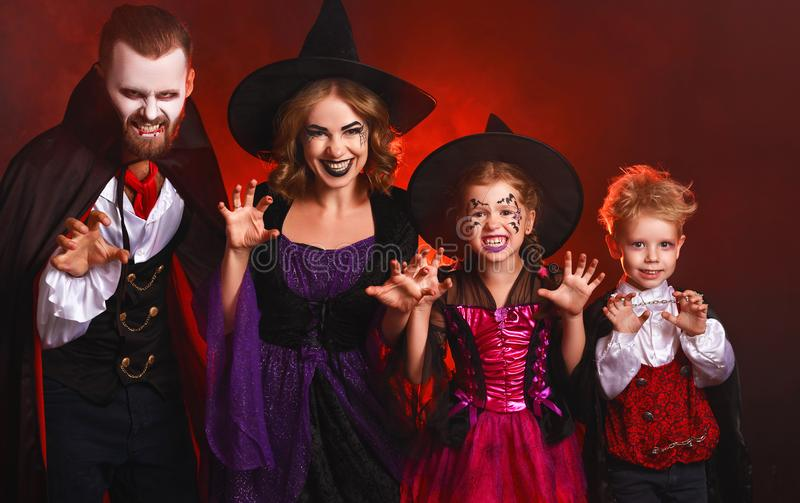 Happy family mother father and children in costumes and makeup on  Halloween on dark red background stock photos