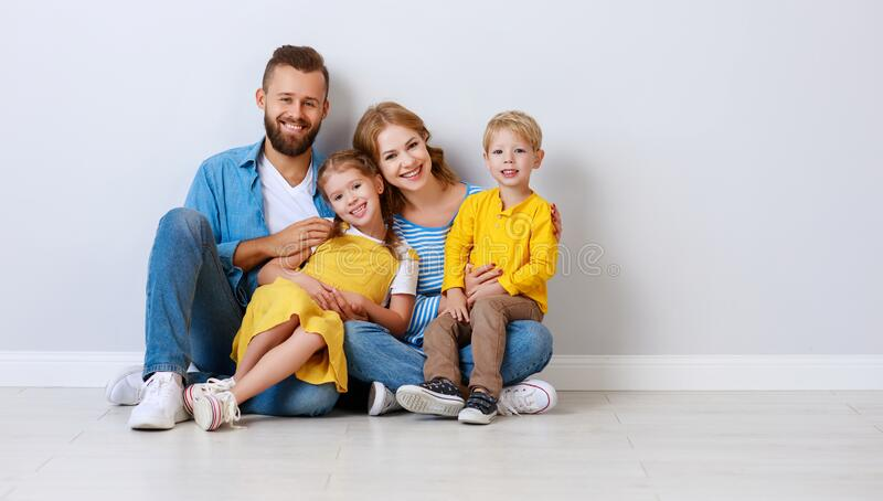 Happy family mother father and children daughter and son  near an empty   blank wall royalty free stock images