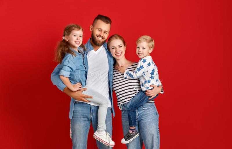 Happy family mother father and children daughter and son  near an   red wall stock photos
