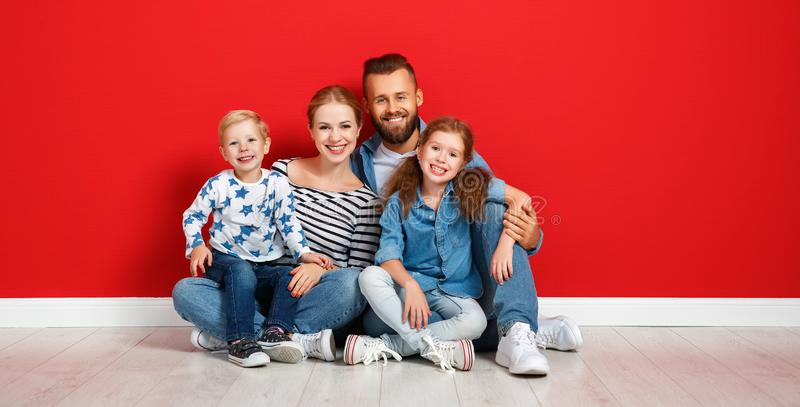 Happy family mother father and children daughter and son  near an   red wall royalty free stock images