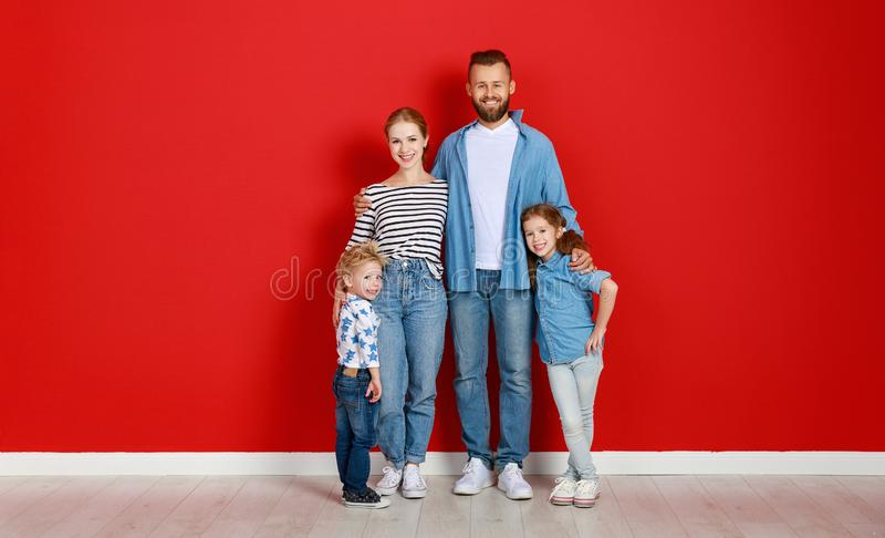Happy family mother father and children daughter and son  near an   red wall stock images