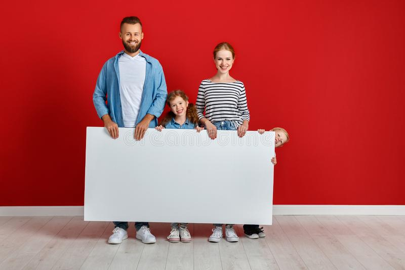 Happy family mother father and children daughter and son  near an   red wall with a white blank poster royalty free stock photo