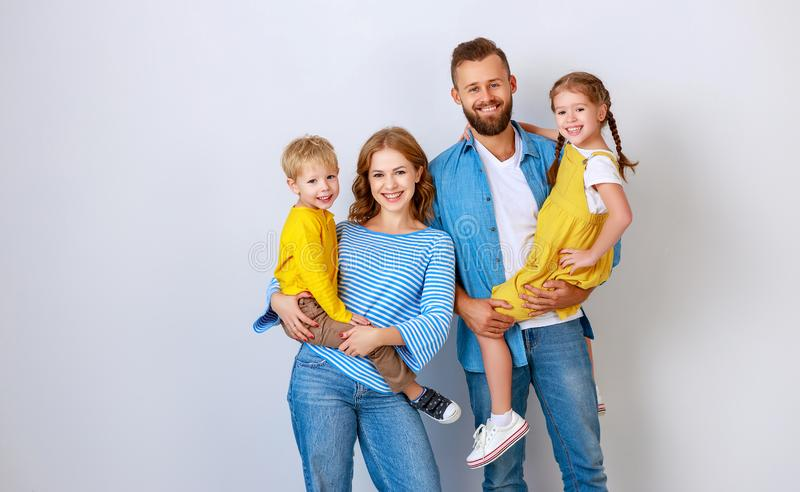 Happy family mother father and children daughter and son  near an   grey blank wall stock image