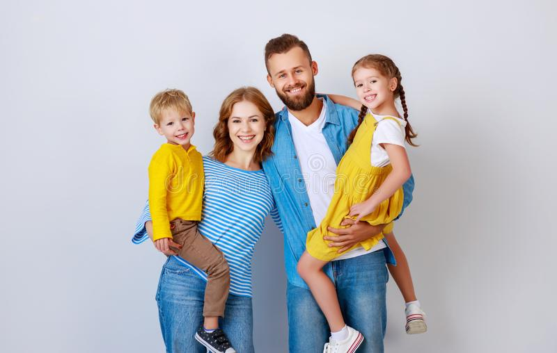 Happy family mother father and children daughter and son  near an   grey blank wall stock photos