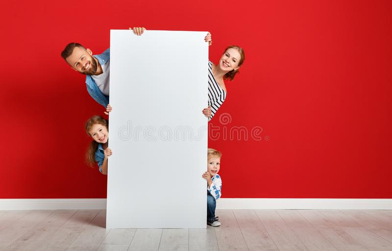 Happy family mother father and children daughter and son  near an   red wall with a white blank poster stock photography