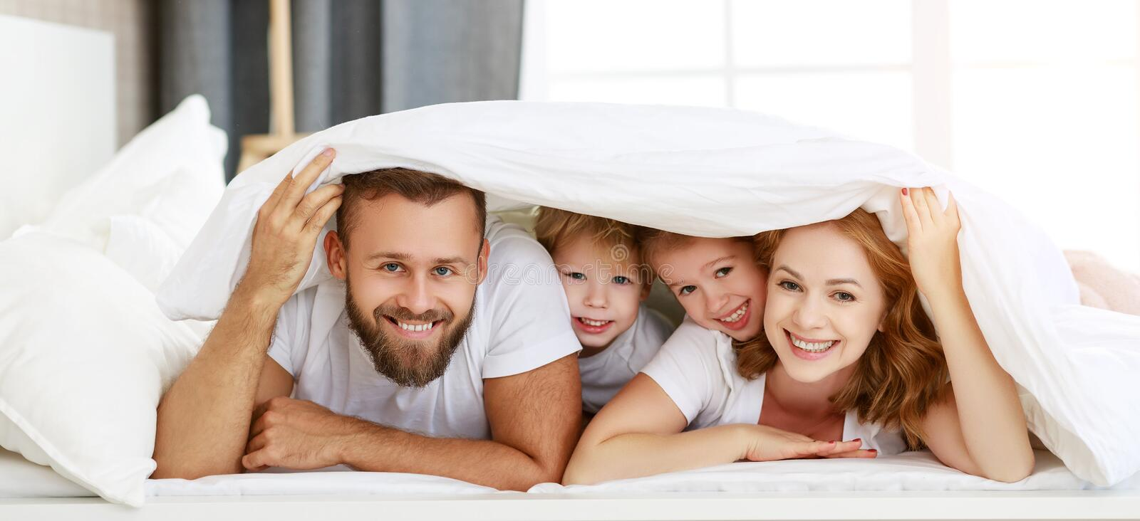 Happy family mother, father and children laughing, playing and smiling in bed   at home royalty free stock images