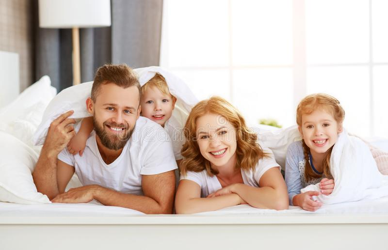 Happy family mother, father and children laughing, playing and smiling in bed   at home stock image
