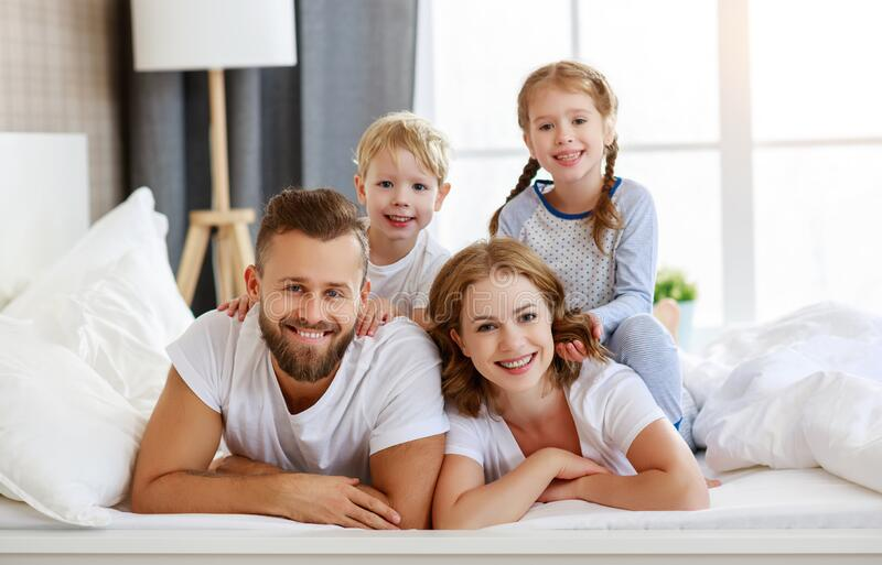 Happy family mother, father and children laughing, playing and smiling in bed   at home royalty free stock photos
