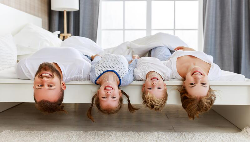 Happy family mother, father and children laughing, playing and smiling in bed   at home stock photo