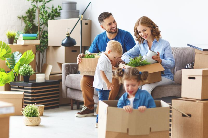 Happy family mother father and children move to new apartment an. Happy family mother father and children move to a new apartment and unpack boxes royalty free stock photography