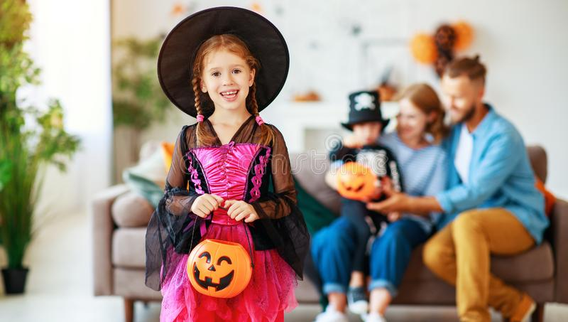 Happy family mother father and children prepare for Halloween in costumes. At home stock photo