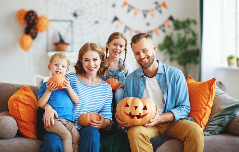 Happy  family mother father and children prepare for Halloween decorate  home with pumpkins,  laughing and  play stock photos