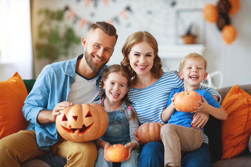Happy  family mother father and children prepare for Halloween decorate  home with pumpkins,  laughing and  play stock photo