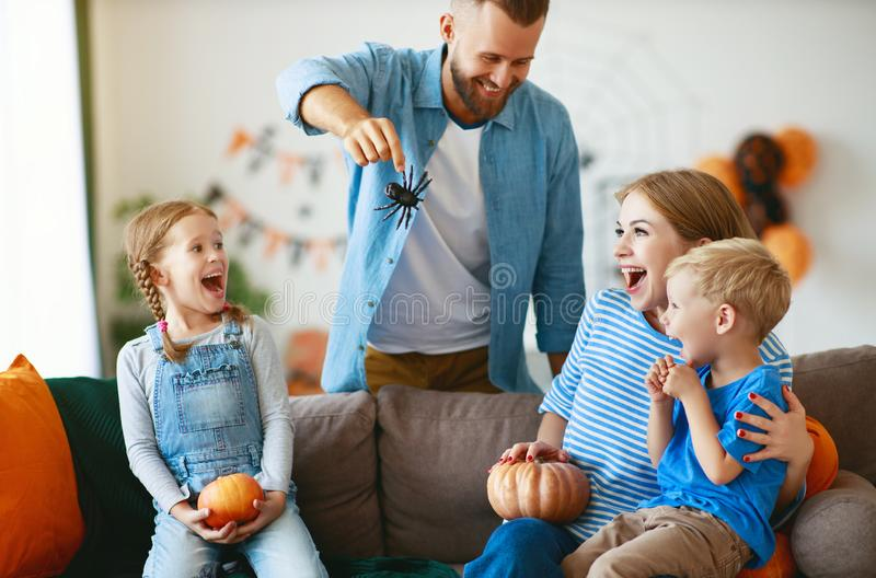 Happy  family mother father and children prepare for Halloween decorate  home with pumpkins and  laughing, play and scare  with stock photos