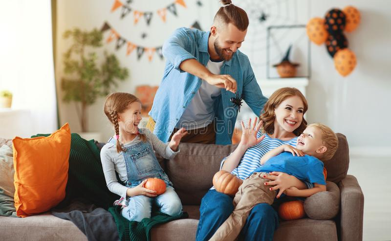 Happy  family mother father and children prepare for Halloween decorate  home with pumpkins and  laughing, play and scare  with royalty free stock photography