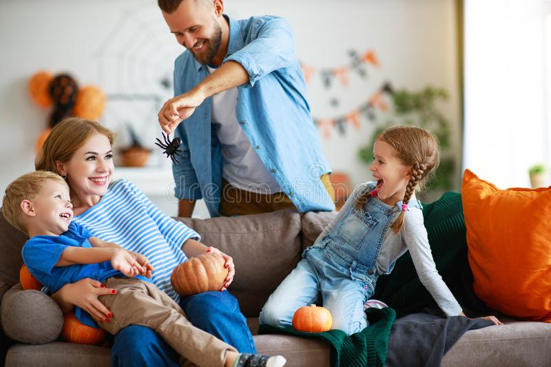 Happy  family mother father and children prepare for Halloween decorate  home with pumpkins and  laughing, play and scare  with royalty free stock images