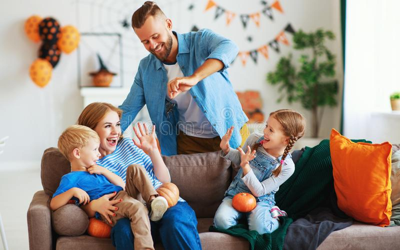 Happy  family mother father and children prepare for Halloween decorate  home with pumpkins and  laughing, play and scare  with stock images