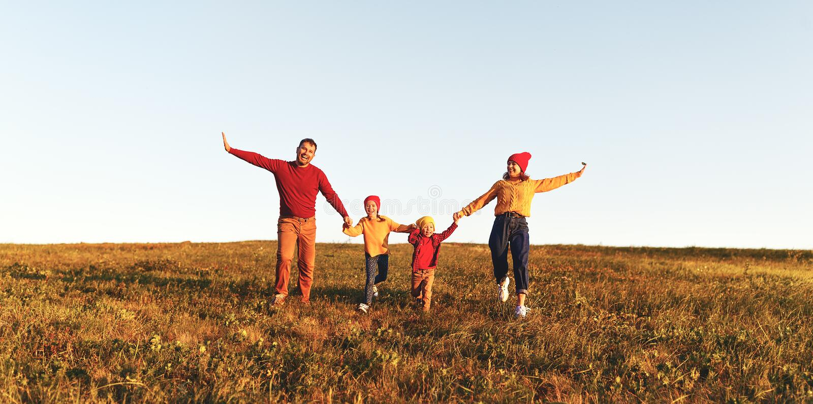 Happy family: mother, father, children son and daughter on autumn sunset stock photo