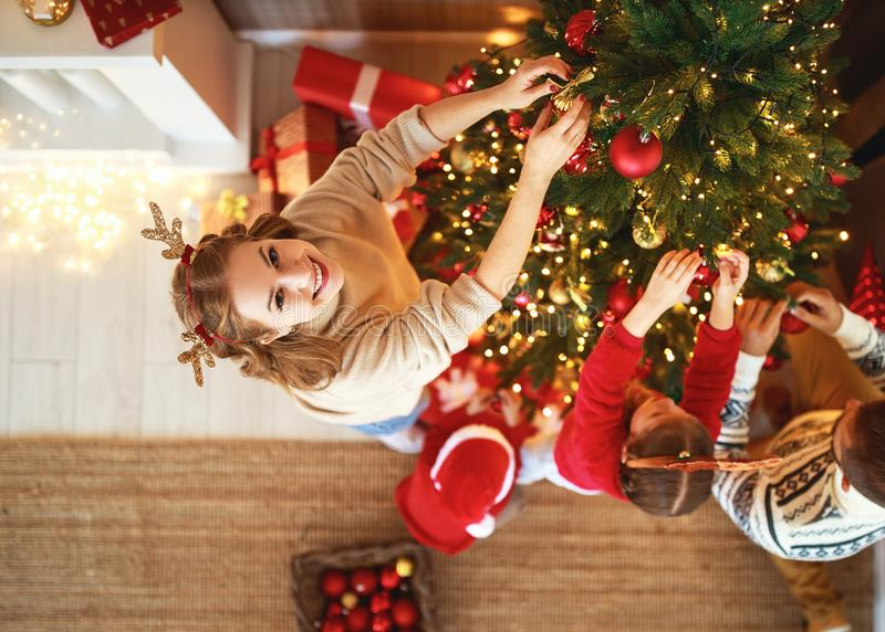 Happy family mother, father and children son and daughter decorate Christmas tree stock images