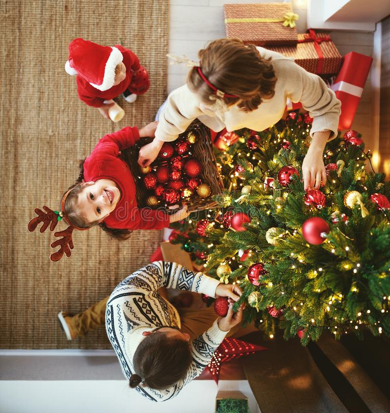 Happy family mother, father and children son and daughter decorate Christmas tree royalty free stock photo