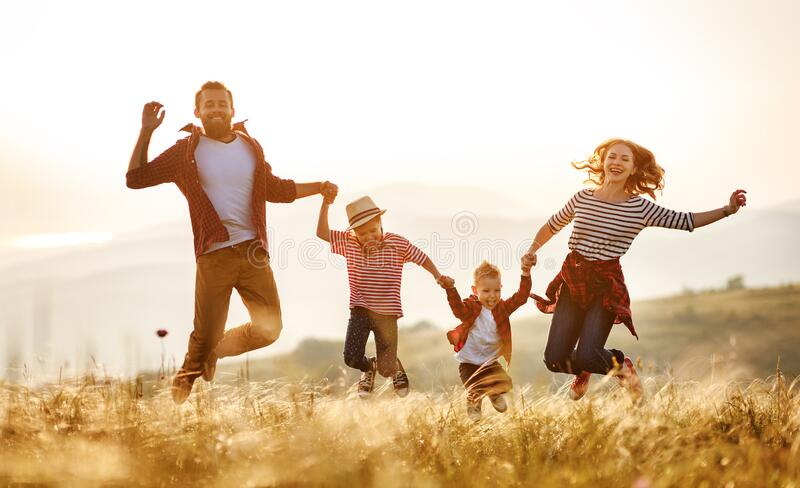 Happy family: mother, father, children son and daughter jumping on sunset royalty free stock image