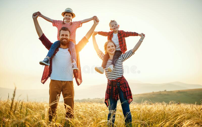 Happy family: mother, father, children son and daughter standing and hugging on sunset stock image