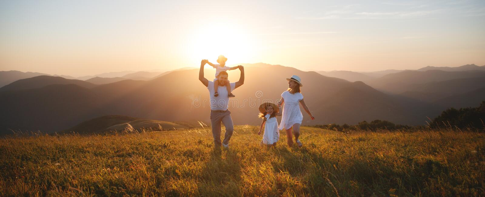 Happy family: mother, father, children son and daughter on sunset. Happy family: mother, father, children son and daughter on nature on sunset royalty free stock photos