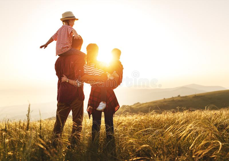 Happy family: mother, father, children son and daughter on sunset. Happy family: mother, father, children son and  daughter on nature  on sunset royalty free stock images