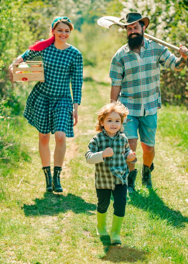 Happy family: mother, father, children son on spring garden background. Farming and agriculture cultivation. Wife and. Husband with son planting in the royalty free stock photo