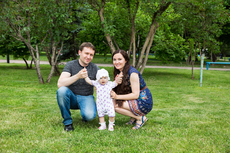 Happy family: mother, father and daughter baby playing stock image