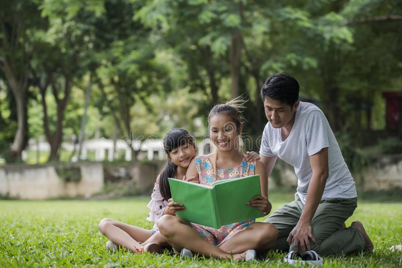 Happy Family mother, father and daughter read a book. In the park stock photo
