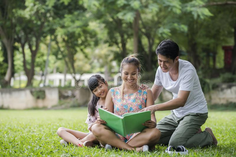 Happy Family mother, father and daughter read a book. In the park stock image