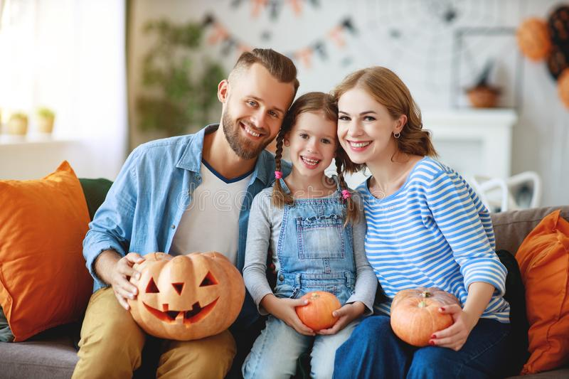 Happy  family mother father and child daughter prepare for Halloween decorate  home with pumpkins,  laughing and  play stock image