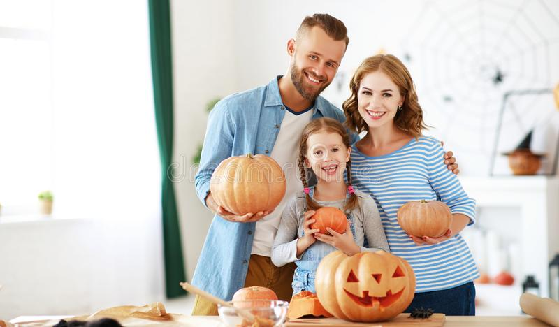 Happy  family mother father and child daughter prepare for Halloween decorate  home with pumpkins,  laughing and  play stock images