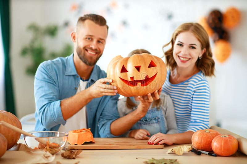 Happy  family mother father and child daughter prepare for Halloween decorate  home with pumpkins,  laughing and  play. Happy  family mother father and hild royalty free stock image